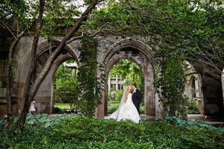 bride-in-an-ines-di-santo-dress-kisses-groom-in-black-tuxedo-in-fourth-presbyterian-church-courtyard