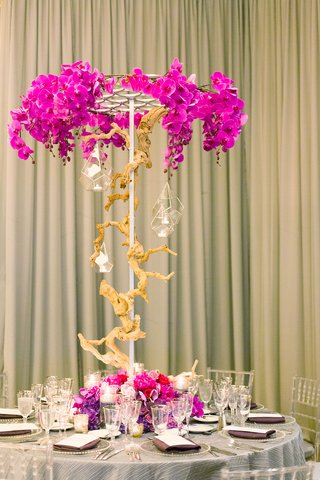 pink-and-purple-orchid-floral-centerpiece-wood-branch-glass-vase-lights-arrangements