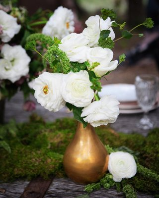 outdoor-wedding-reception-table-with-moss-a-golden-vase-full-of-white-flowers-and-greenery