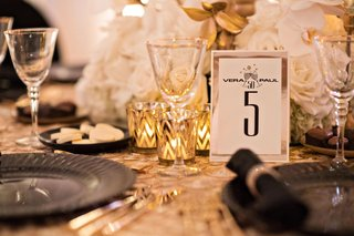 wedding-reception-gold-linen-black-plate-champagne-design-on-table-number-chevron-candle-votives