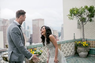 alexis-cozombolidis-and-hunter-pence-during-first-look-on-balcony-in-san-francisco-skyline-grey-suit
