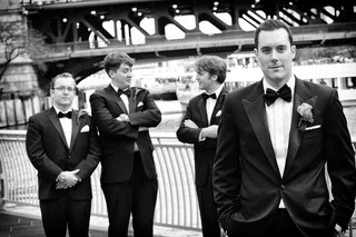 black-and-white-photo-of-groom-and-groomsmen-in-tuxedos-by-chicago-river