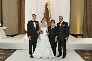 bride-and-groom-in-ceremony-ballroom-with-mom-and-dad