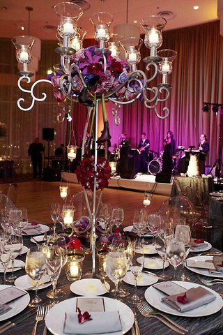 purple-flowers-on-top-of-candleholder-at-ballroom-reception