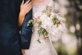 bride-holds-grooms-arm-and-carries-rustic-wedding-bouquet