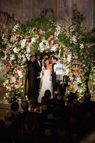 bride-and-groom-in-tallit-under-floral-chuppah
