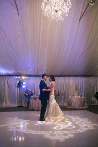 bride-in-reception-wedding-dress-with-groom-during-first-dance-at-tent-wedding-with-purple-lighting