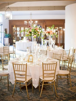 gold-chiavari-chairs-indoor-wedding-reception-garden-theme-tall-flower-arrangements-centerpieces