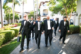 groom-and-groomsmen-walking-through-venue-bow-ties-suits-tuxedos-dress-shoes-black-sunglasses