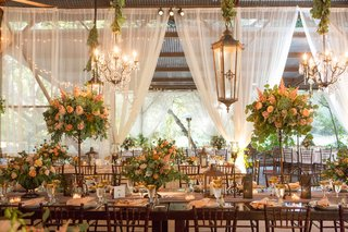 wedding-reception-long-wood-table-high-low-centerpiece-chandeliers-green-garlands-drapery-rafters