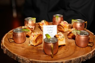 cocktail lobster rolls and moscow mules on wood slab serving board cocktail hour wedding