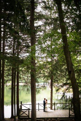 wedding-location-new-york-summer-camp-feel-bride-groom-portrait-on-dock-deck-tall-trees-forest