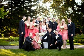 bride-and-groom-with-bridesmaids-in-pink-dresses-and-groomsmen-in-black-tuxedos-at-a-country-club