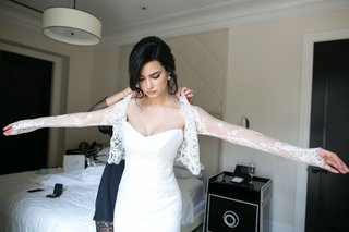 bride-getting-help-in-bridal-suite-strapless-wedding-dress-with-long-sleeve-lace-bolero-illusion