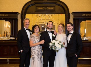family-portrait-at-wedding-grooms-family-portrait-in-front-of-bar