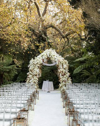 hotel-bel-air-wedding-ceremony-outdoor-white-flower-arch-with-gold-lanterns-clear-chairs-white-aisle