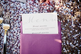 wedding-reception-sit-down-dinner-menu-in-purple-napkin-on-sequined-tablecloth