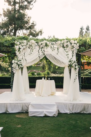 white-drapery-wedding-ceremony-structure-chuppah-ivory-flowers-greenery-white-stage-grass-lawn