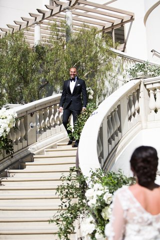 first-look-at-monarch-beach-resort-in-dana-point-southern-california-groom-walking-down-steps-bride
