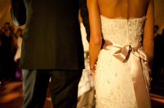 bride-and-groom-back-of-white-wedding-dress-with-pink-bow-and-black-tuxedo
