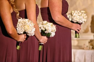 bridesmaids-in-purple-strapless-dresses-hold-bouquets-of-white-roses-calla-lilies-wrapped-in-purple