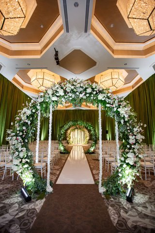 wedding-ceremony-ballroom-circle-arch-flowers-greenery-white-flower-ropes-white-aisle-chairs