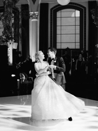 black-and-white-photo-of-bride-and-groom-first-dance-twirl-ball-gown-at-vibiana-wedding-venue