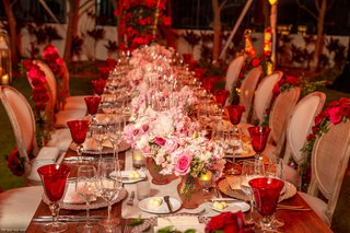 wedding-reception-long-wood-table-pink-flower-centerpiece-red-goblets-roses