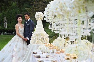 bride-in-ines-di-santo-julia-groom-in-midnight-blue-tuxedo-look-upon-large-cake-decorated-table