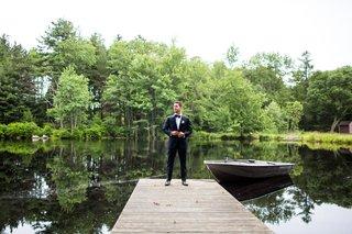 wedding-portrait-of-groom-standing-at-end-of-dock-cedar-lakes-estate-row-boat-new-york