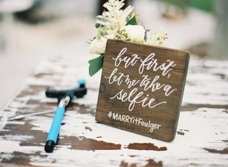 shabby-chic-wedding-wood-sign-with-calligraphy-wedding-hashtag-and-selfie-stick-on-cocktail-table
