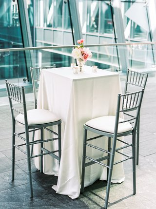 high-silver-gray-chairs-white-table-linen-small-candles-blush-ivory-flowers-urban-background