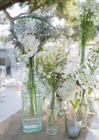 white-and-green-wildflower-arrangements-in-glass-vases-on-woven-table-runner-white-linens