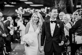 black-and-white-photo-of-bride-and-groom-walking-up-aisle-after-outdoor-ceremony-guests-smiling