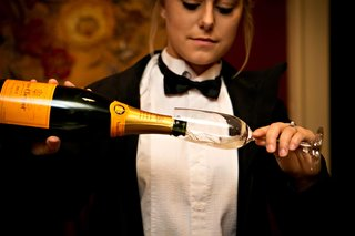 server-in-black-bow-tie-pouring-veuve-clicquot-champagne-into-champagne-flute-glass