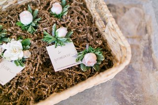 basket-filled-with-pink-rose-and-green-leaf-boutonnieres-for-groomsmen
