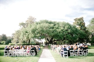wedding-reception-under-large-tree-up-on-steps-stone-white-flower-petal-aisle-white-chairs-guests