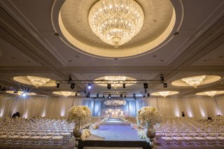 opulent-white-ceremony-space-ballroom-florals-aisle-ghost-chairs-california-indian-hindu-wedding