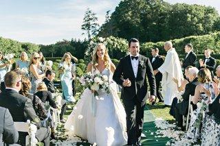 bride-in-angel-sanchez-wedding-dress-and-groom-in-tuxedo-hold-hands-oheka-castle-wedding-ceremony
