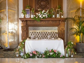sweetheart-table-by-fireplace-mantel-decorated-with-lanterns-and-flowers-settee-tufted-rectangular