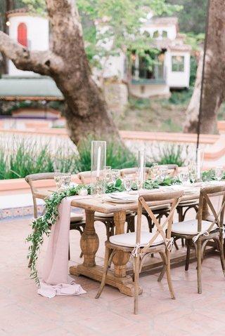 wedding-reception-outdoor-courtyard-wood-table-vineyard-chairs-blush-linens-greenery-candlesticks