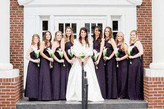 bride-in-ball-gown-and-fur-wrap-stole-with-bridesmaids-in-dark-purple-bridesmaid-dresses-calla-lily