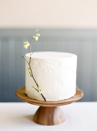 simple-single-tier-cake-on-wooden-stand-with-a-sprig-of-corylopsis