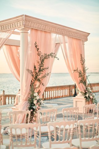 ornate-chuppah-with-blush-drapery-and-greenery-crawling-up-the-sides