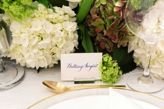 brides-escort-card-with-blue-calligraphy-new-last-name-gold-rim-charger-and-gold-spoon-hydrangeas