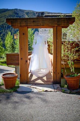 long-sleeve-wedding-dress-hanging-from-mountain-lodge