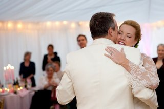 bride-and-groom-in-white-dance-at-tented-wedding-reception