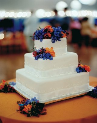 white-cake-with-blue-and-orange-fresh-flower-topper