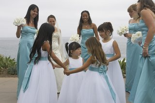 flower-girls-in-white-dresses-hold-hands-in-circle-surrounded-by-bridesmaids-in-blue-dresses