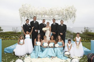 turquoise-and-white-bridal-party-in-front-of-white-flower-chuppah